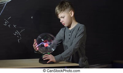 Boy playing with a Tesla generator with static electricity