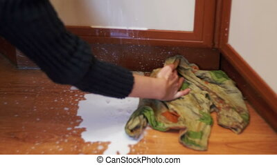 Cleaning the Kitchen Floor with a Cloth from the Spilled...