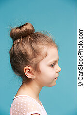 Cute little girl on a blue background close-up - The profile...