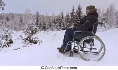 Disabled man on wheelchair using professional photo camera...