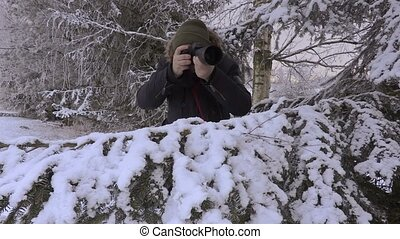 Man with professional photo camera near spruce in winter