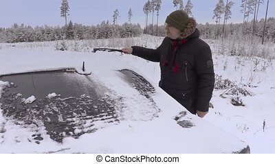 Man cleaning car window from the snow in winter