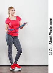 Woman wearing sportswear standing on weight machine -...