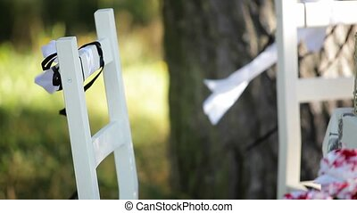 White wooden chair outdoors with ribbons at windy day