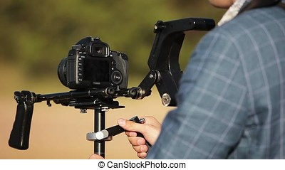 Cameraman working with camera and steadicam outdoors