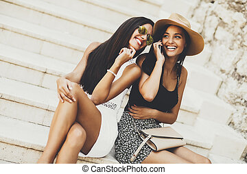 Two women sitting on the stairs outside and using mobile phone