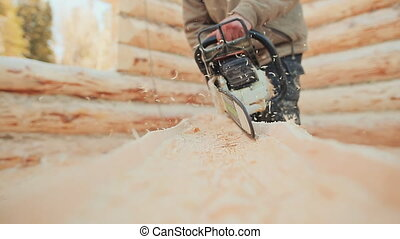 Joiner working chainsaw sawing logs for wooden houses....