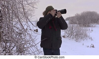 Man take photos on professional photo camera in winter
