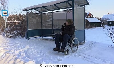 Disabled man on wheelchair talking on phone and check time...