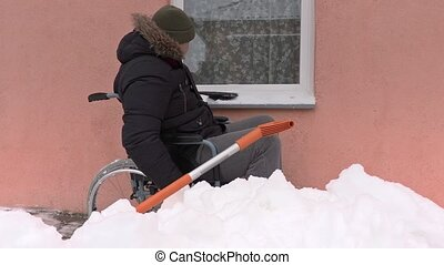 Disabled man on wheelchair cleaning window in winter