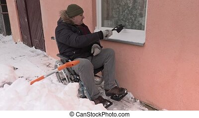 Disabled man on wheelchair cleaning window from the snow