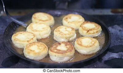 cheese cakes fried in a pan - cheesecakes round shape fried...