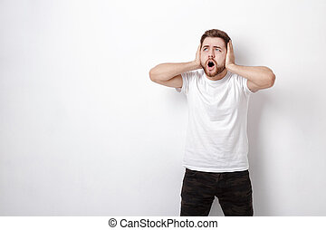 indignant young man with dark hair and beard in t-shirt...