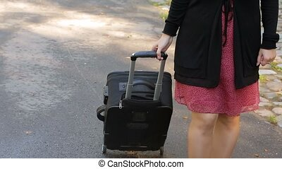Woman with suitcase bag on wheels unrecognizable