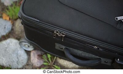 Woman opens suitcase - Woman opens black suitcase outdoors