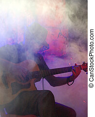 folk guitarist immersed in the lights and smoke during a...