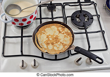 Cooking pancakes on Shrove Tuesday in a special pan in the...