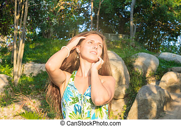 beautiful girl in a green dress on sunset