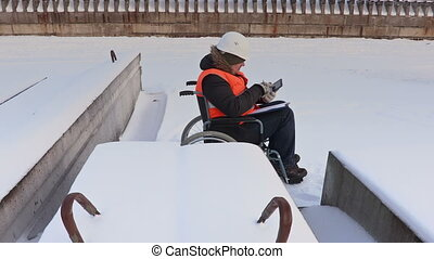 Disabled worker on wheelchair using tablet and writing