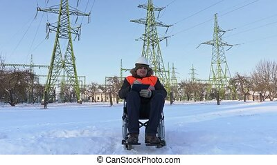 Disabled worker on wheelchair writing under high-voltage...