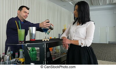 Bartender pouring cocktail from shaker for a girl at the bar
