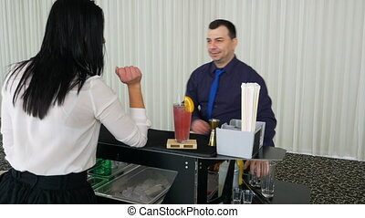 Woman ordering two shots and waiting for the barman to prepare her drink