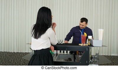 Bartender mixing cocktail shots drinks for woman waiting at...