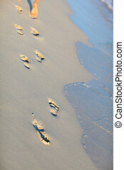 Footprints on tropical beach - Footprints closeup on white...