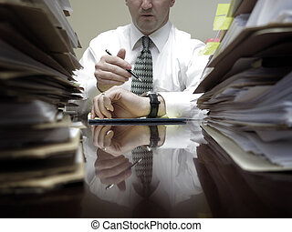 Businesman at Desk with Piles of Files and Papers -...
