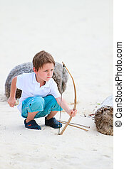 Cute boy playing with bow and arrows - Cute boy playing...