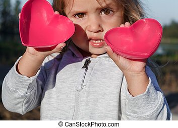 little girl playing with a red plastic heart. she holds it in her hands