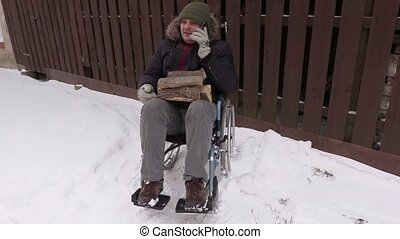 Disabled man on wheelchair with firewood logs talking on...