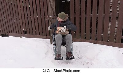 Disabled man on wheelchair with firewood logs near the barn