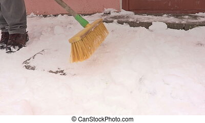 Man clean path from the snow near door