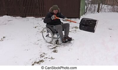 Disabled man on wheelchair working with snow shovel