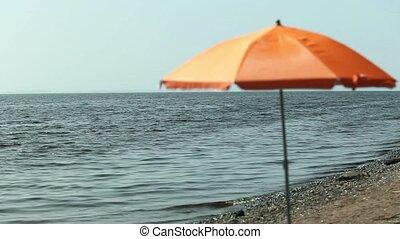 seascape parasol on empty beach - beach umbrella on an empty...