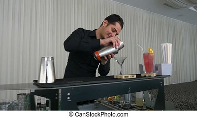 Bartender pouring mixed drink cocktail from shaker into a...