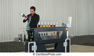 Bartending show with barman pouring multiple alcoholic cocktails shots at once