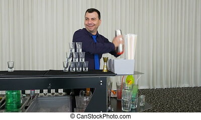 Bartender pouring drinks from shaker into tower shots