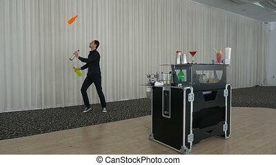 Bartender juggling three bottles at a bar and making...
