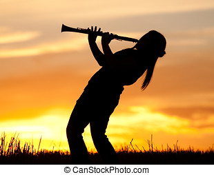 Playing the Clarinet at sunset. - A silhouetted woman plays...