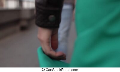 Young man and woman go to meet each other, their hands momentarily touch. close-up, slow motion.
