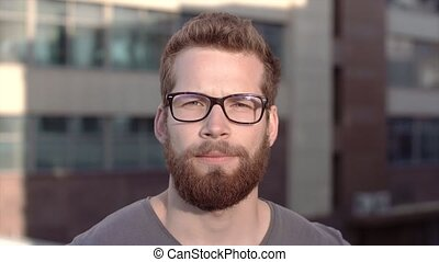Portrait of young smiling handsome bearded men in glasses on...