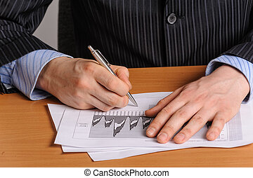 Analizing business chart - Businessman with pen analysing...