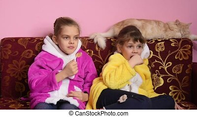 Girls sit on the sofa, lick lollipops and watch TV, the TV...