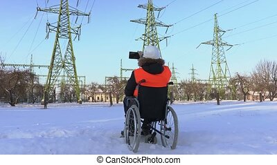 Disabled worker take pictures near to high-voltage lines