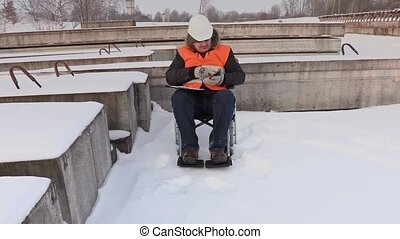 Disabled worker on wheelchair using tablet PC