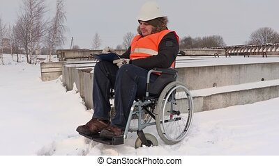 Disabled worker on wheelchair checking building materials