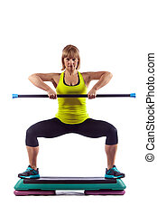 Fitness woman is exercising with the crossbar. Isolated on...
