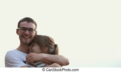Young beautiful couple of lovers tenderly embrace, smiling and laughing at sunset.